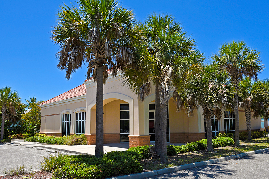 Exterior of a Vacant Commercial Building for Sale or Lease with Palm Trees in Front