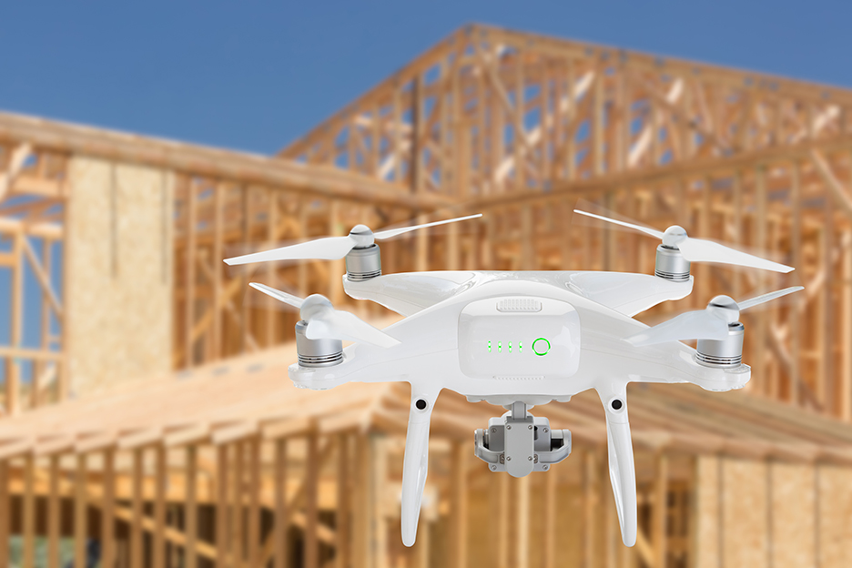 A white, photography drone flying in front of a new house being constructed.