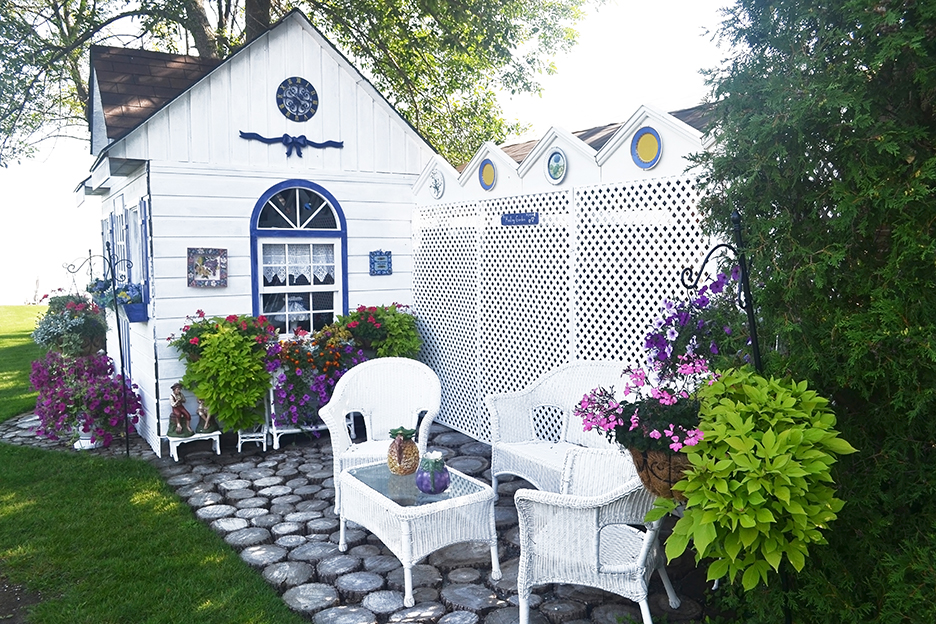A beautiful small garden shed with nice chairs surrounded by flowers and plants.